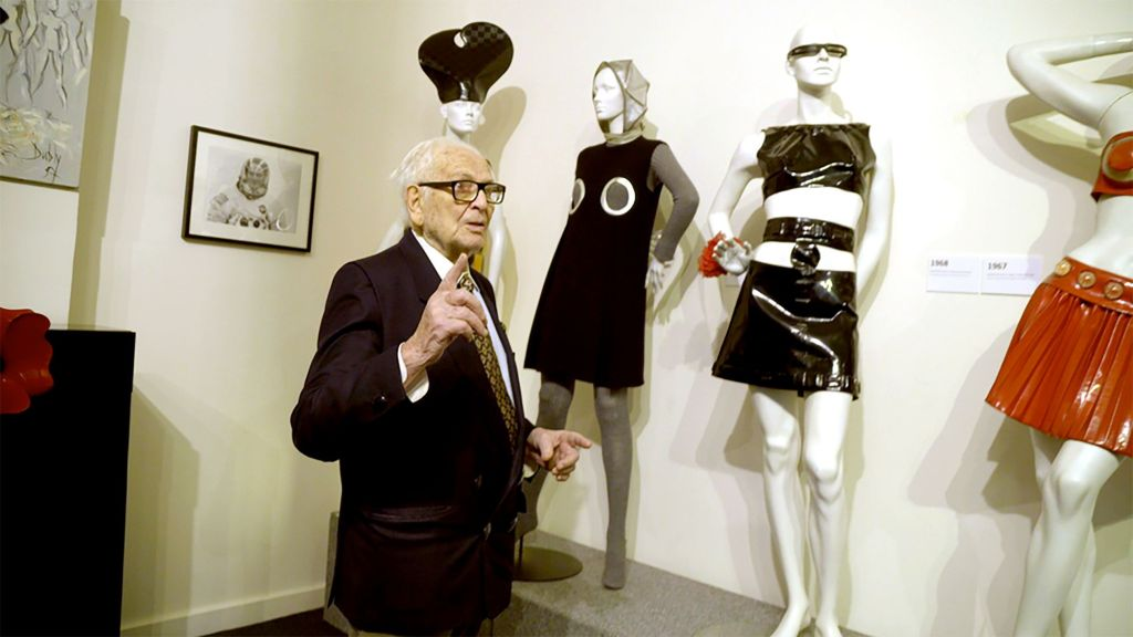 A still from documentary 'House of Cardin'. The image shows legendary designer Pierre Cardin, now an elderly man, showing filmmakers around a retrospective of his iconic work from the 60s.