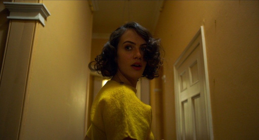 A still from 'The Banishing'.  Marianne (Jessica Brown Findlay) is seen centre frame, close-up, she is in a corridor and looking behind her with a shocked expressions. she is wearing a yellow woolen top and her dark curled hair is cropped short and full of volume. It looks like she is being followed or has heard something behind her.
