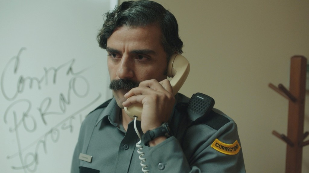 A still from short film 'The Letter Room'., Richard (Oscar Issac) is shown in his Corrections Facility uniform, in an office, on the phone. He is shown in close-up, the reciever to his ear, looking away contemplatively. He has dark, greying hair and a thick moustache, he is in his 40s.