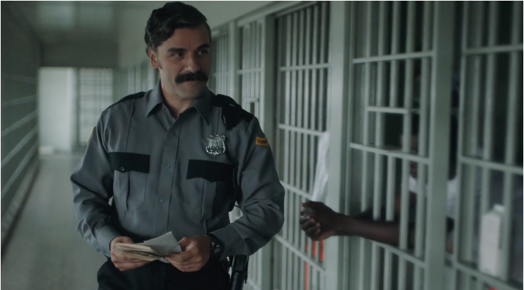 A still from short film 'The Letter Room'.  Richard (Oscar Issac) is shown in a mid-shot, to the left of the frame. He is a Prison officer walking past some cells, one pair of arms is clasped through the bars, relaxed. He is smiling towards an unseen inmate. He wears a khaki and black officers uniform and has wavy dark hair and a thick black moustache, he carries a small pile of letters in his hand.