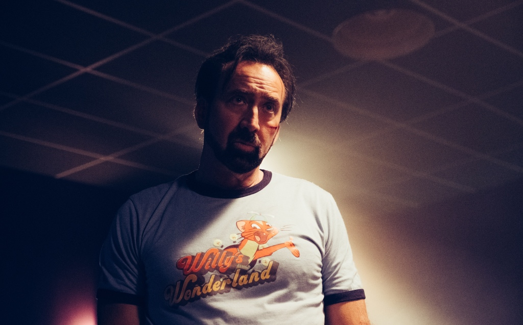 A still from 'Willy's Wonderland'. Nicolas Cage is shown in mid shot, darkly lit from behind, he has facial hair and a cut on his cheek. He wears a blue 'Willys Wonderland' ringer t-shirt and looks to the right of the image at something in front of him off screen.