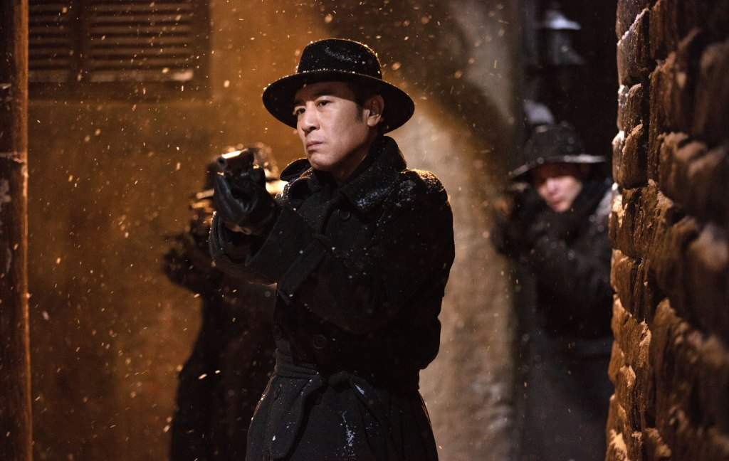 Still from Cliff Walkers. A man stand centre frame, wearing a trilby style hat and a long black coat. He is pointing a gun at something off camera. Snow falls, constrasted sharply again his clothes. The background is out of cous, but two figures dressed similarly stand behind him pointing guns in the same direction. Light from above bathes the image in a  golden glow.