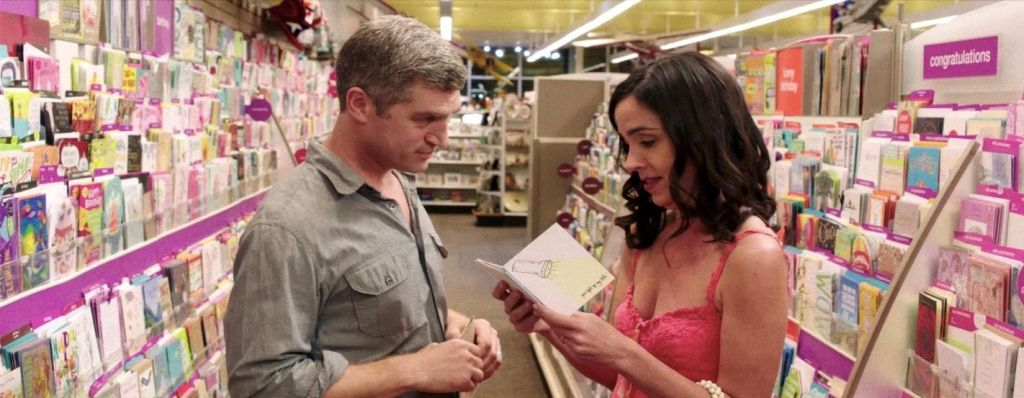 A still from 'Before/During/After'.  David (Jeremy Davidson) and Jennie (Finnerty Steeves) are stood centre frame, in a pink-covered card shop, picking out cards for each other. Jennie is reading the message inside one she is holding as Jeremy looks on intently.