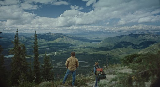 A still from 'Cowboys'. Troy (Steve Zahn) and his son Joe (Sasha Knight) are standing on the edge of a cliff, looking down over a lush, mountainous landscape, with a cloudy sky.