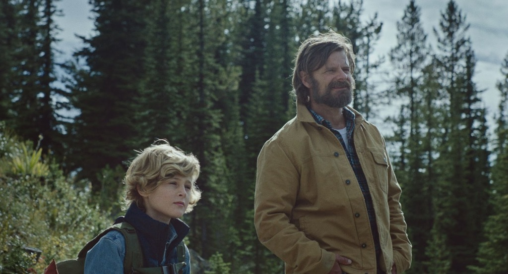 A still from 'Cowboys'. Troy (Steve Zahn) is pictured right, with his son, Joe (Sasha Knight) amongst a tree-filled wilderness background. Troy wears a tan open jacket with a plair shirt underneath, he is in his 40s and has chin-length dirty blonde hair and a full beard. Joe is a pre-teen, curly blonde hair and wearing a denim jacket with a padded gilet over, carrying a large green backpack.