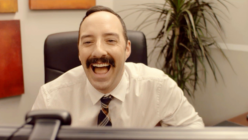 Still from Eat Wheaties! Tony Hale, as Sid Straw sits in front of a computer screen that is just visible at the bottom of the image. He is laughing, frozen in a moment of slightly unhinged glee. With a large moustache and brown tartan tie, he looks out of time with the more modern office setting.