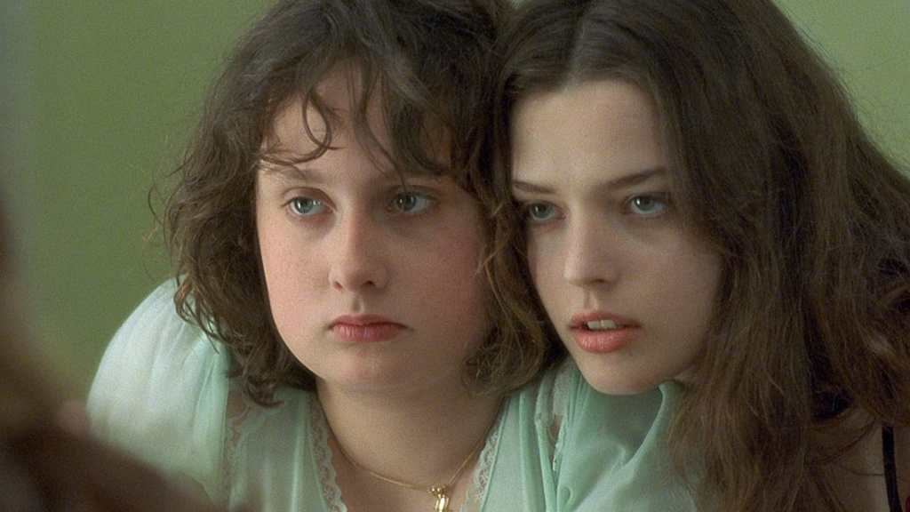 A still from 'Fat Girl'. Sisters Anais (Anais Reboux) and Elena (Roxane Mesquida) are shown centre frame in close-up, their heads are pressed together and they are looking at themselves in a mirror. Anais is a bigger girl, with a chubby face and short curly brown hair. Elena is slimmer, dainty features and long flowing brown hair.