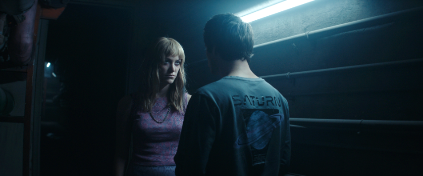 A still from 'Flashback'. Fred (Dylan O'Brien) has his back to the camera, talking to Cindy (Maika Monroe) in a basement. The image is darkly lit and Cindy's face is menacing.