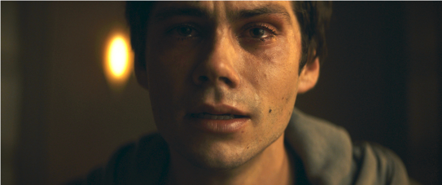 A still from 'Flashback'. Fred (Dylan O'Brien) is shown centre frame, in close up, crying. His mouth is slightly agape and his brow furrowed, there is a light behind his left ear.