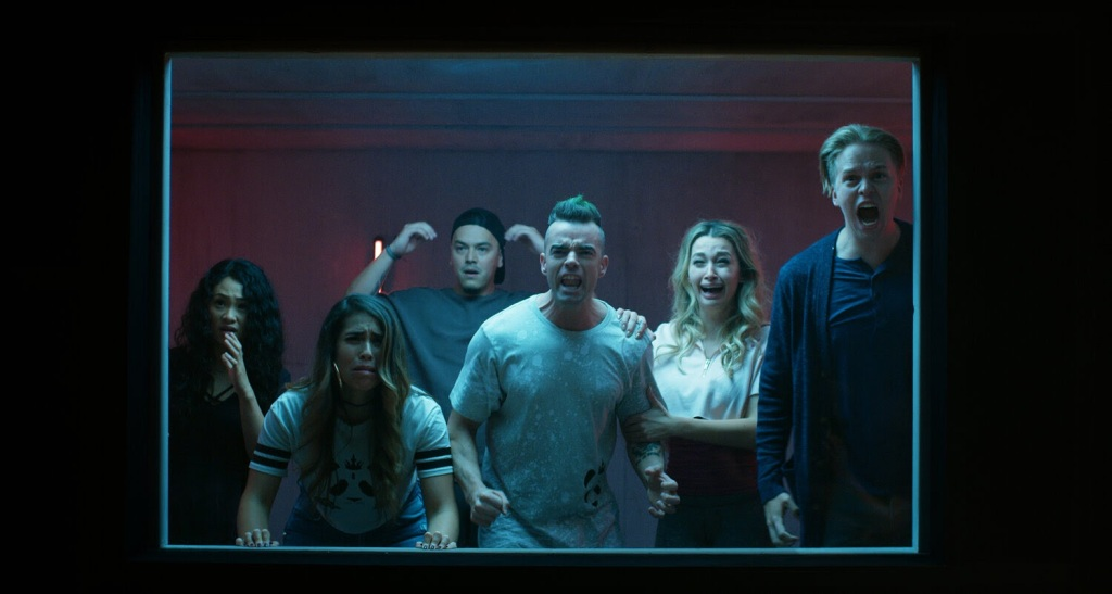 A still from 'Funhouse' A group of 20-somethings, a mixture of men and women, are stood behind a window lit by a neon blue light. it is as if they are looking into a room that we can't see, they are all shouting and screaming.