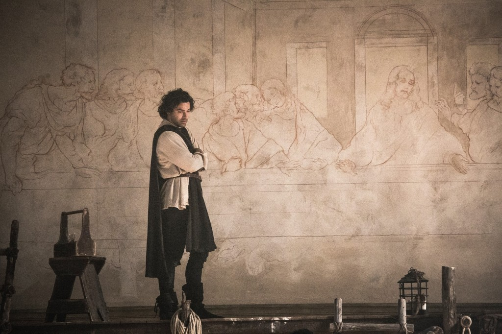 A still from 'Leonardo'. Da Vinci (Aiden Turner) is shown in a wide shot against the backdrop of an emerging sketch of famous paint 'The Last Supper'. He has his arms folded and is looking down,.