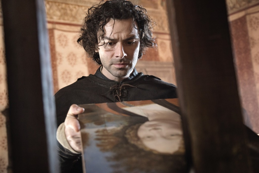 A still from 'Leonardo'. Da Vinci (Aidan Turner) is shown through two wooden bars, he is examining a portrait with a furrowed brow.