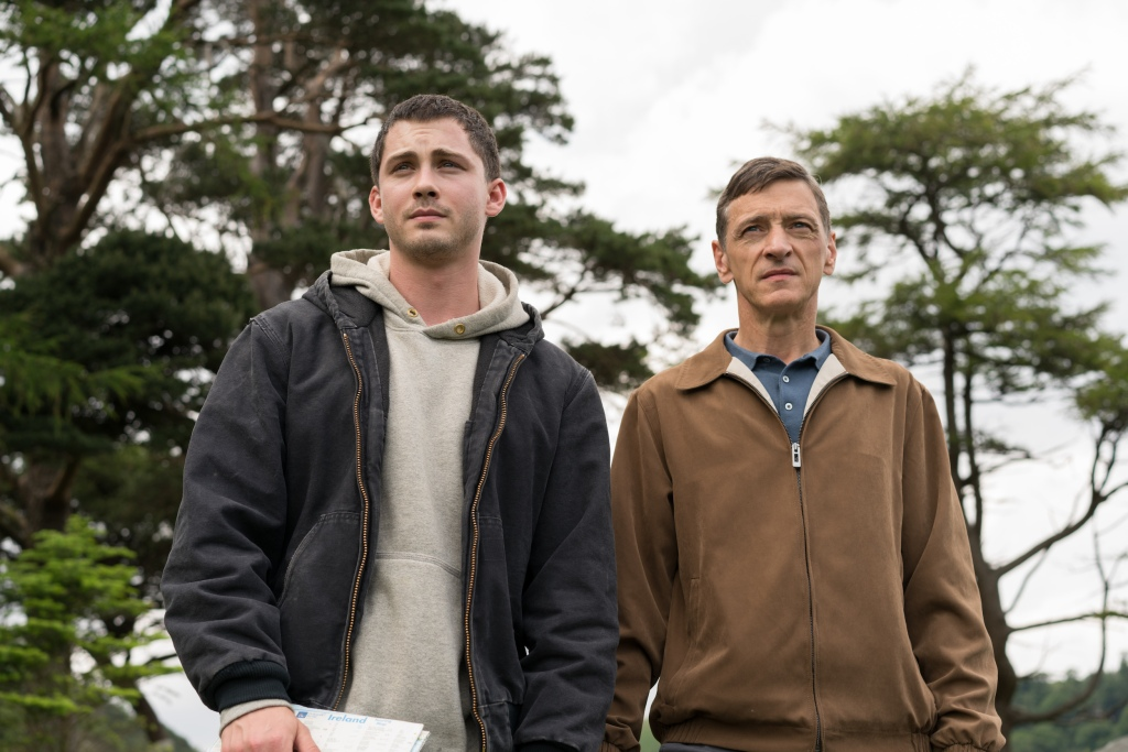 A still from 'End of Sentence'. Sean (Logan Lerman) and his father Frank (John Hawkes) stand centre frame, in a mid shot, outside near some trees. Sean is a young man in his late 20s wearing a grey hoodie and black jacket, he is holding some documents. His father squints forward wearing a blue zipped up jackey, mid 50s.