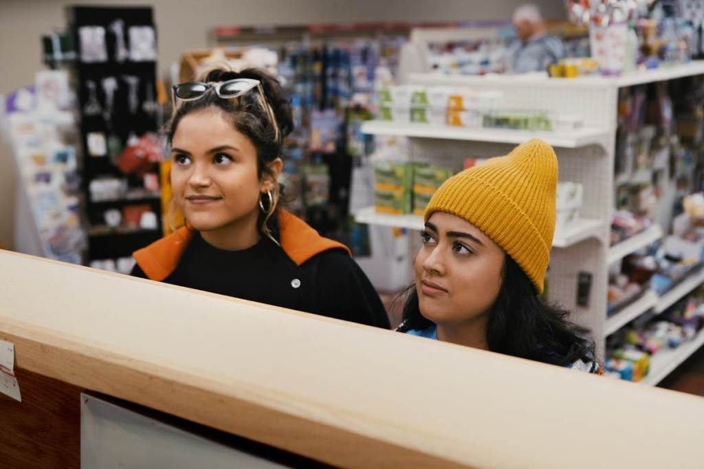 A still from 'Plan B'. Lupe (Victoria Morolos) and Sunny (Kuhoo Verna) are shown in a pharmacy at the counter, looking to an out of shot character.
