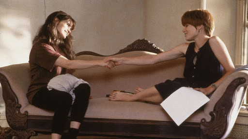 A still from 'Single White Female'. Hedy (Jennifer Jason Leigh) and Allie (Bridget Fonda) are sat on an orante lounge chair, one at either end, they are holding hands across the middle space and smiling at each other.