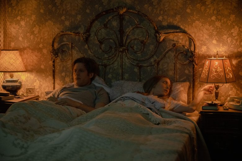 Still from Things Heard and Seen. James Norton and Amanda Seyfreid lie in a bed with an ornate iron head board. Two bedside lamps light the room with a warm glow, highlighting the ugly patterned wallpaper.