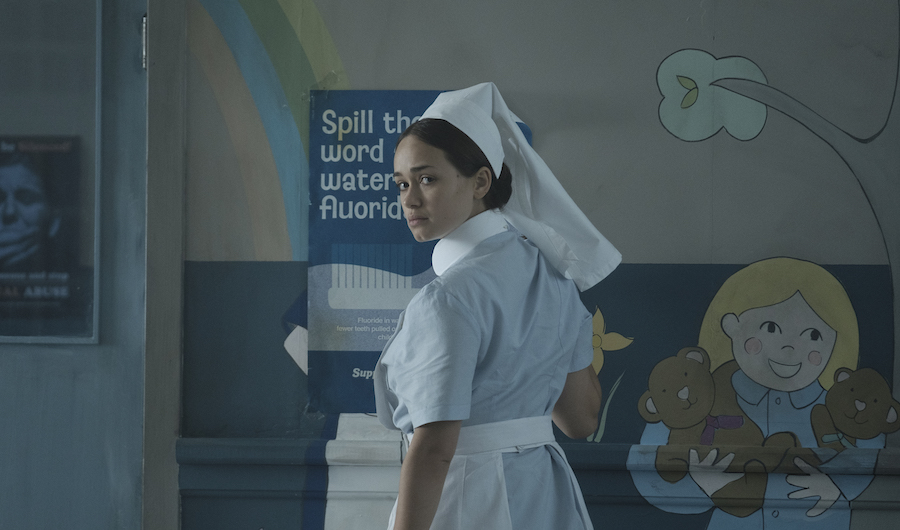 A still from 'The Power'. Val (Rose Williams) is a nurse in 1970s Britain, she is wearing her uniform and standing in a room in the children's ward, there is posters on the wall and a mural of a girl holding two teddy bears. Val is looking behind her.