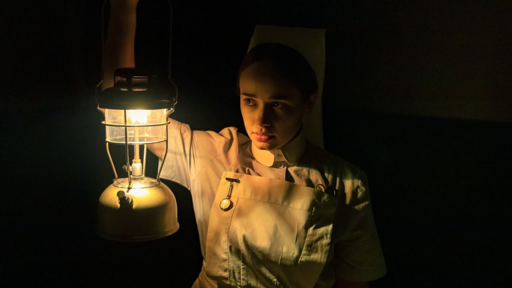 A still from 'The Power'. Val (Rose Williams) is a nurse in 1970s Britain, she is wearing her uniform and walking through a pitch-black corridor lit only by a lantern. Her dark hair is pulled back and she looks ahead with aprehension.