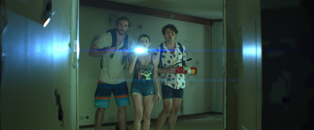 A still from 'The Resort'. Three friends, one girls stood in between two boys, are walking through what looks like an abandoned building. The girl is shining a torch in a doorway, everyone's faces are shocked.