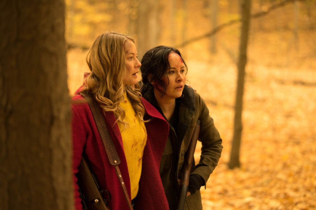 A still from 'The Retreat'. Valerie (Sarah Allen) and Renee (Tommie-Amber Pirie) are shown just off centre frame, in a mid shot. They are in a wooded area in the autumn time and emerging from behind a tree to the left. Valerie has a gun over her shoulder and the pair both have their mouths open in shock.