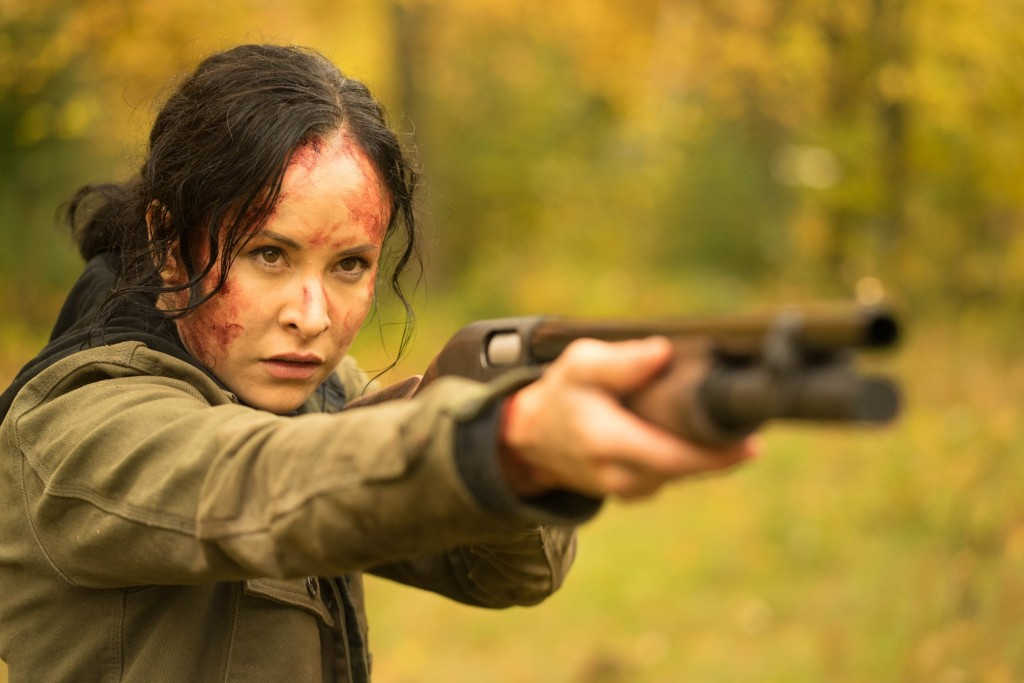 A still from 'The Retreat'. Renee (Tommie-Amber Pirie) is shown to the left of the frame, in a close-up, pointing a gun that fills the rest of the image. She is in a woodland area and her face covered in blood, her dark hair is pulled back in a ponytail and caked in sweat and blood.
