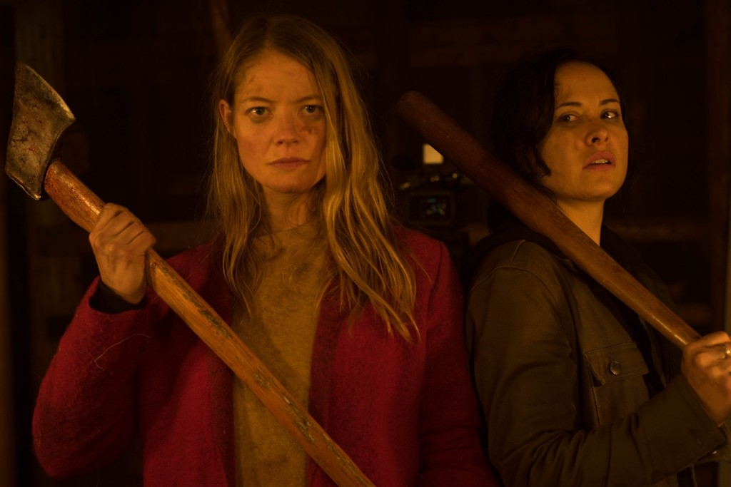 A still from 'The Retreat'. Valerie (Sarah Allen) and Renee (Tommie-Amber Pirie)  are shown centre frame, mid-shot, both wielding axes, their faces speckled with blood and dirt. Their faces are determined.