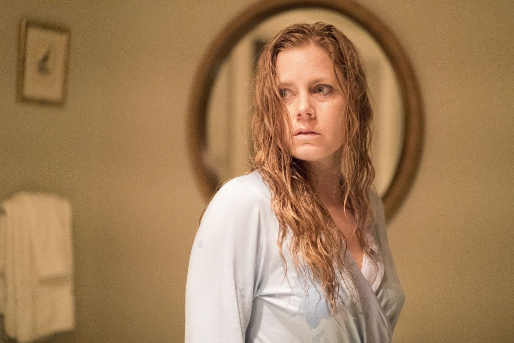 A still from 'The Woman in the Window' Anna Fox (Amy Adams) is shown in mid shot, just off centre frame. She is standing in a bathroom, beige wallpaper and a mirror behind her head, a towle hangs off the wall. Anna is wearing a loose night shirt and looking over one shoulder, scared. Her red hair is wet and her face gaunt and pale.