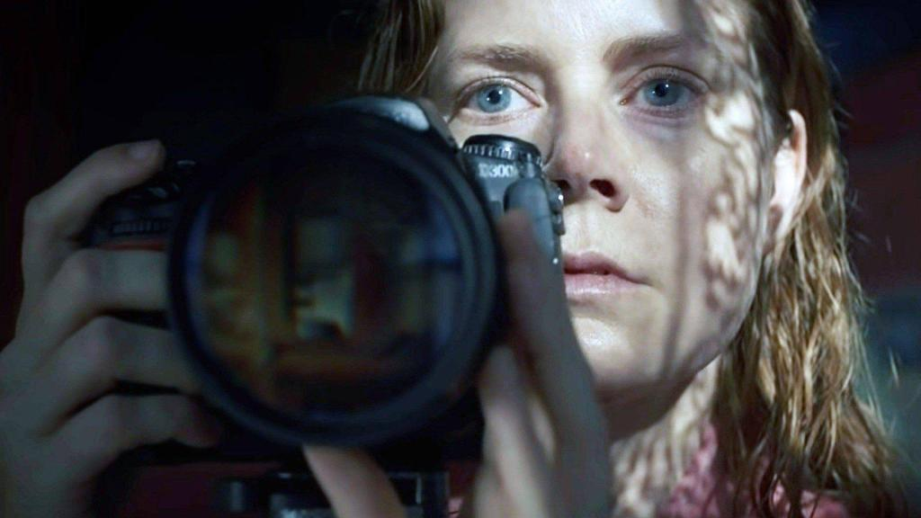 A still from 'The Woman in the Window'. Anna Fox (Amy Adams)  is shown centre frame, in close up holding a DSLR camera. Her face is in focus, pale and scared, there's a sheen of sweat across her face and her red hair is wet and slicked back.