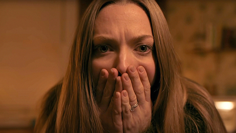 Close up on Amanda Seyfreid. She is staring directly at the camera, eyes wide in horror. Her hands are clasped over her mouth. The background is out of focus, and the right side of a her face is slightly in shadow.