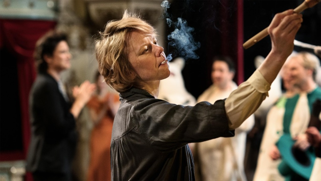 A still from 'Tove'. Tov Jansson (Alma Poysti) is shown centre frame, smoking a cigarette and reaching out of frame with a paintbrush. There is a group of people stood behind her paying her no mind.