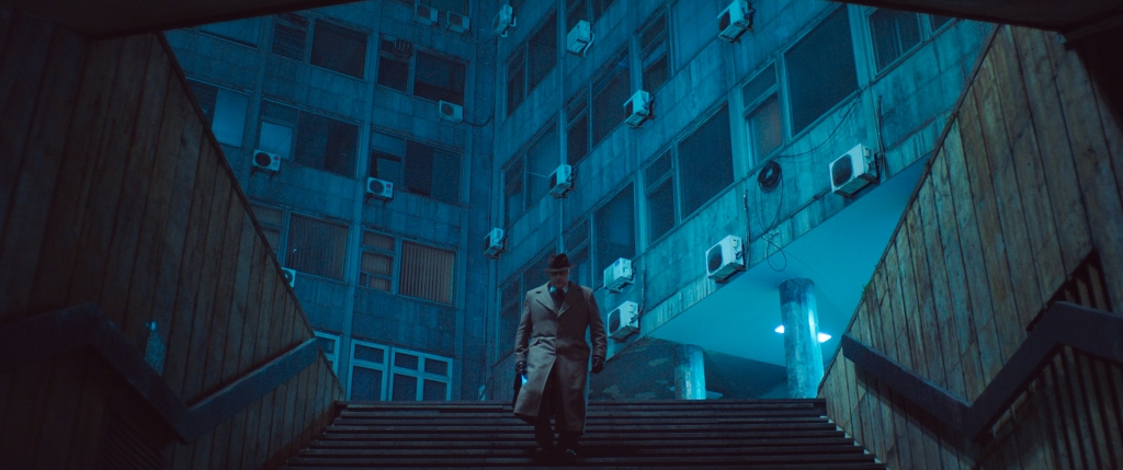 A still from 'Undergods'. A man is shown walking down some steps into an underpass, the image is shrouded in blue tones. Shot from below you can see a large set of apartments in the background, the air conditioning monitors having an ominous presence.