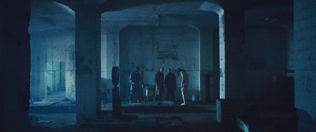 A still from 'Undergods'. Three man are shot from a distance, dressed in all black they are looking at a fourth naked man, standing shivering. They are in an abandoned, disused space with large columns throughout the room that frame the shot.