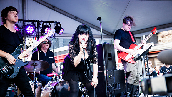 Still from the film: Lydia Lunch is centre of the image, with a black dress and hair, holding a microphone and looking directly into the camera. Surrounding her are a band, two men with guitars either side and a man on the drums in the background.