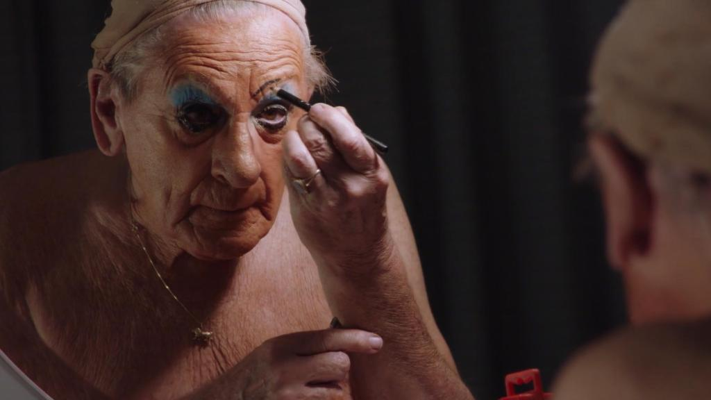 Maisie Trollette aka David Raven sits putting on drag makeup: sharply pencilled, arching eyebrows, heavy blue eyeshadow and foundation. He is looking into the mirror determinedly, and the background around is black.