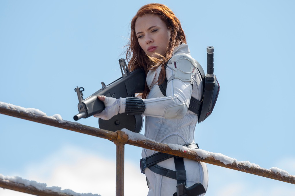 Natasha dressed in a white tactical spy suit holding a massive gun over a railing, which is covered in snow.