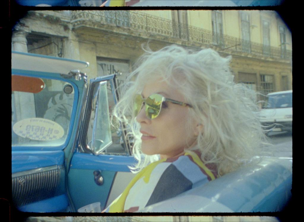 Still from Blondie: Vivir En La Habana. Debbie Harry, hair tousled in the wind, sits in an open-topped car in Havana, looking way from the camera in yellow mirrored sunglasses. Shot on 16mm, the film is visible in the image.