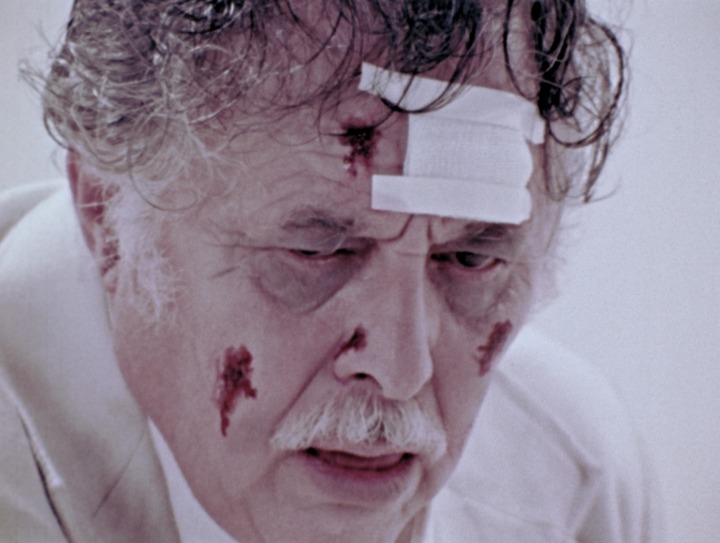 A still from 'The Amusement Park'. An elderly man is shown in close-up, centre frame. His face is covered in bloody wounds and a bandage taped to his forehead. His eye bags are dark and he looks exhausted, his sweaty hair sticking to his head.