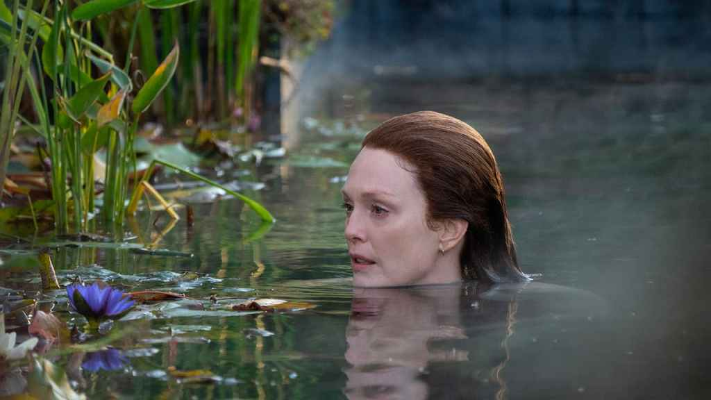 Julianne Moore as Lisey. She is submerged in a pond with only her head sticking out of the water. A purple flower floats about a foot away from her face. Long grass surrounds her.