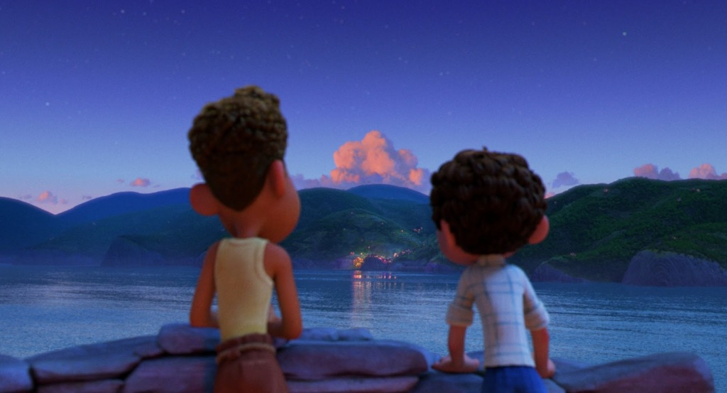 A still from animated film 'Luca'. Luca (Jacob Tremblay) and Alberto (Jack Dylan Grazer) are shown from behind, leaning over a rock wall, looking over a body of waterto a hilly landscape at the shore, a house is lit up and the sun sets behind the mountains.