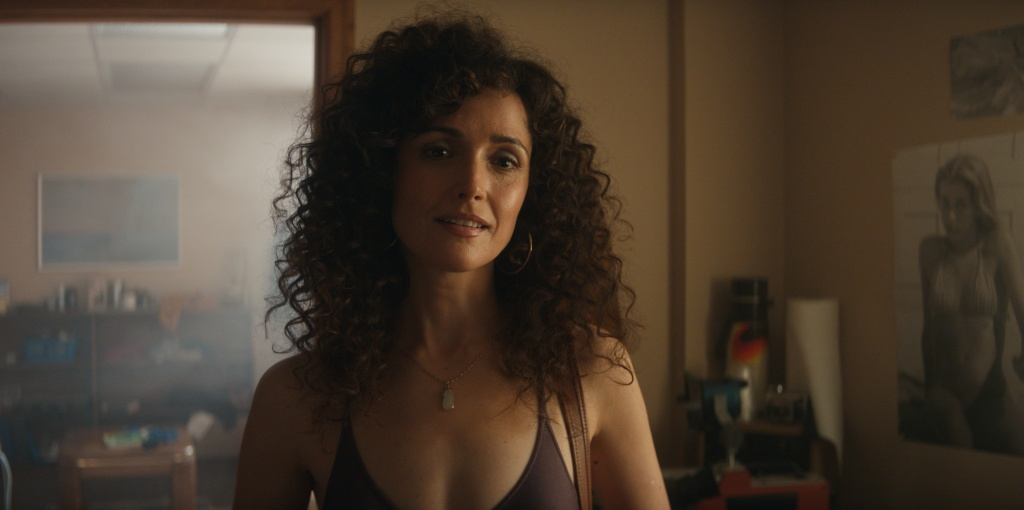 Rose Byrne as Shelia in Physical. She stands in what looks like an office space. She has big curly brown hair with a friendly/inquisitive expression.