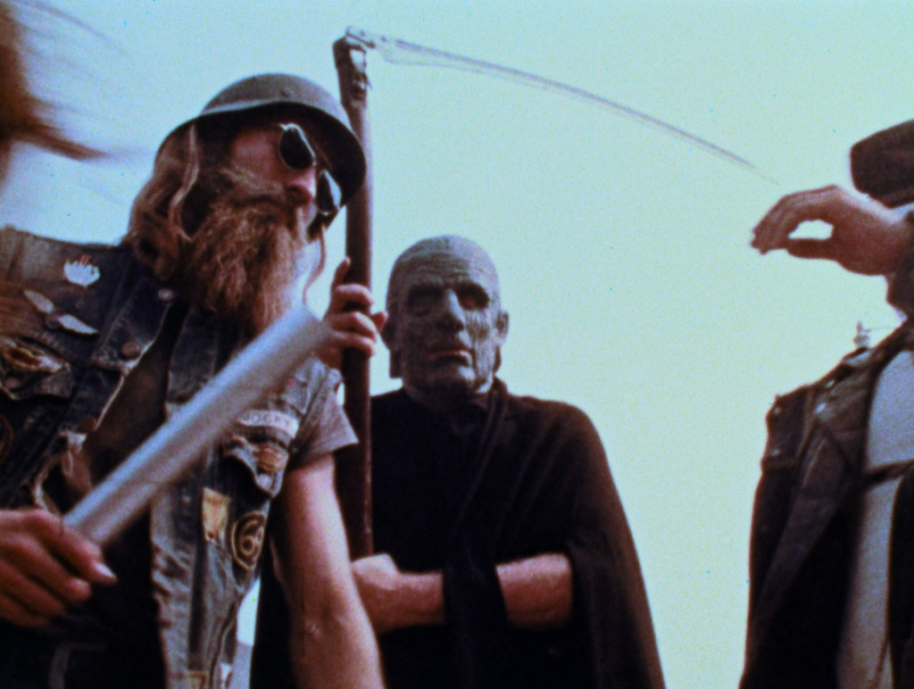 A still from 'The Amusement Park'. A youngman in a biker denim cutoff jacket covered in patches is in the left of the image, holding a baton, wearing dark glasses and a soldier's helmet, in the middle is a man dressed as the grim reaper, wearing a latex mask.
