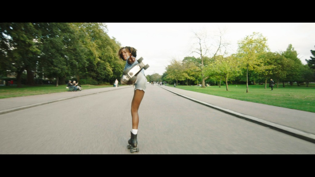 Still from Stormskater. A young black woman is in the centre of the image, standing on one leg. The other is stretched out towards to camera, and only the wheels of the skate are showing, blurred. Behind her stretches a quiet road, surrounded by grass and trees.