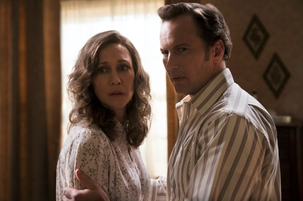 A still from 'The Conjuring: The Devil Made Me Do It'. Lorraine and Ed Warren (Vera Farmiga and Patrick Wilson) are stood in a mid-shot, centre frame, Ed clutching Lorraine as they both look on with concern. They are stood in a living room in the late 70s and a window is behind them.