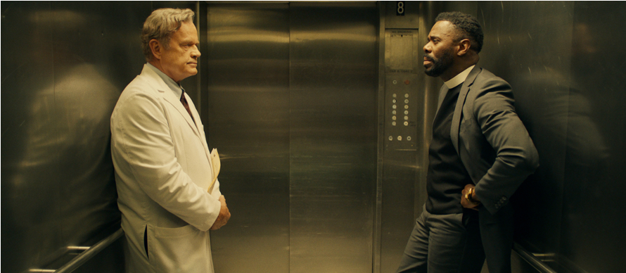 A still from 'The God Committee'. Two men, One in a surgeons coat and the other a vicar, stand in an elevator facing each other.