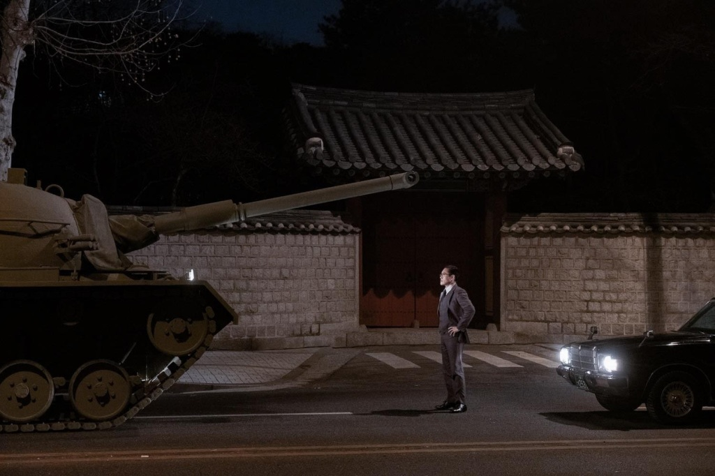 A still from The Man Standing Next'. A man stands on the roadside, dwarfed by an army tank in front of him. He stands in a suit, hands on his hips, illuminated by the car headlights behind him.