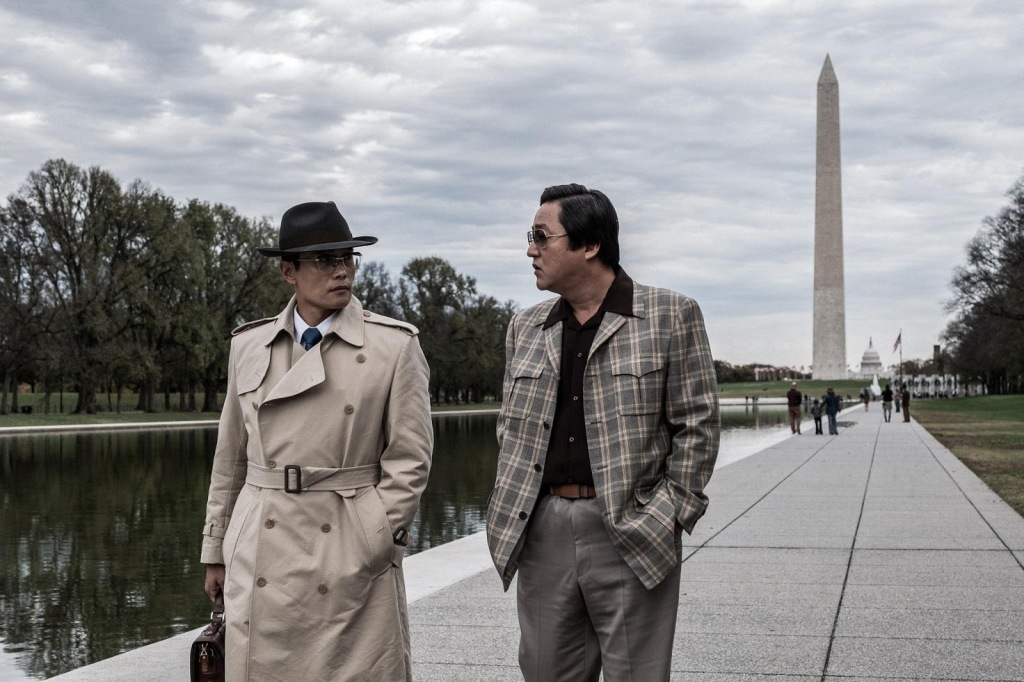 A still from 'The Man Standing Next'. Two Korean men are in Washington DC walking alongside the pond leading down to Washington Monument. One is dressed in typical 1970s spy fashion in a trench coat and fedora, carrying a briefcase. The other is wearing a plaid jacket and grey pants with his hands in his pockets.