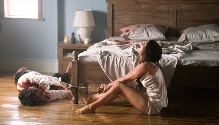 A still from 'Till Death'. Emma (Megan Fox) is shown in a wide shot, sat on the floor by a large wooden king size bed, handcuffed to a dead and bloodied man on the floor. She is wearing a satin set of pajamas and screaming, tugging on the handcuffs.