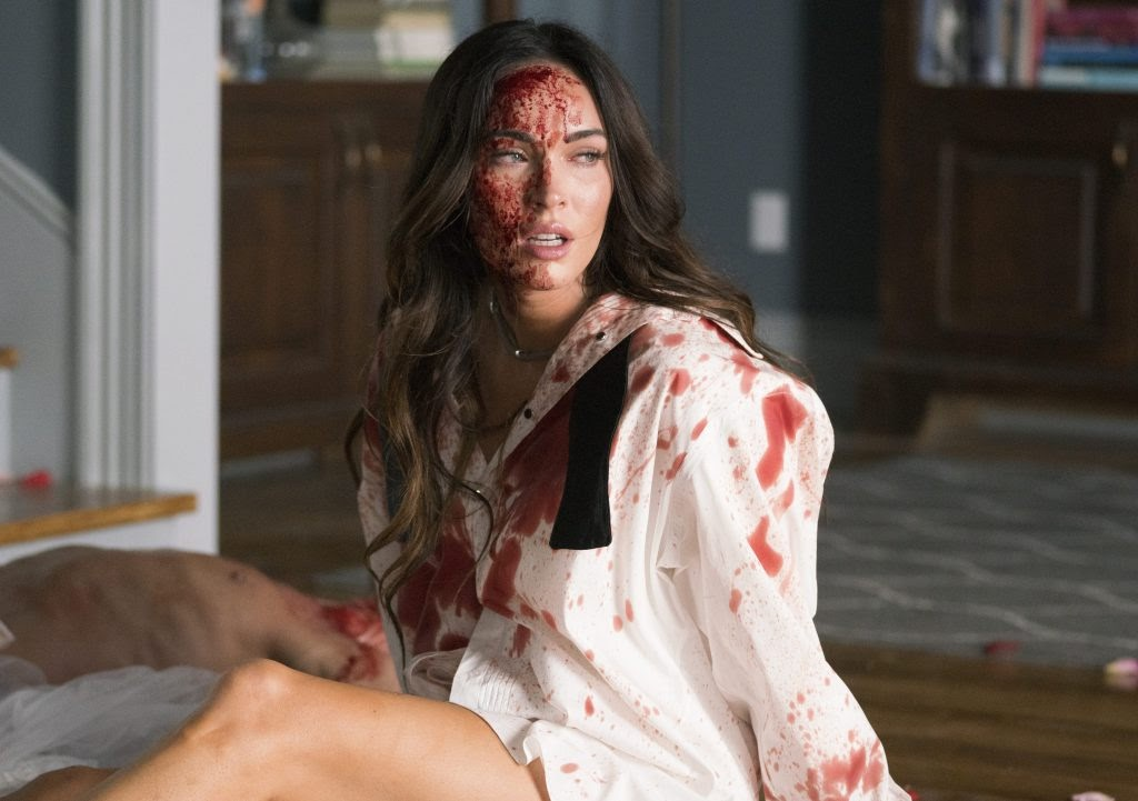 A still from 'Till Death'. Emma (Megan Fox), is shown centre frame, in a mid shot. She is sat at the bottom of some stairs wearing a white shirt and loose bow tie, covered in blood. The shirt is doused as is her face, her beautiful curled hair still falls gracefully around her face. A man's naked body is visible in the bottom left hand side of the image.