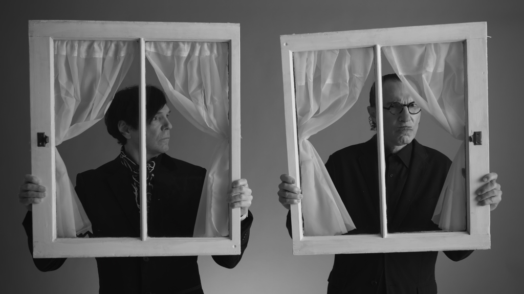 Still from The Sparks Brothers. Ron and Russell Mael Stand next to each other, Russell is on the left, looking at Ron who is staring straight into the camera, pouting comedically. They are both holding up window frames with net curtains tied back. The image is black and white.
