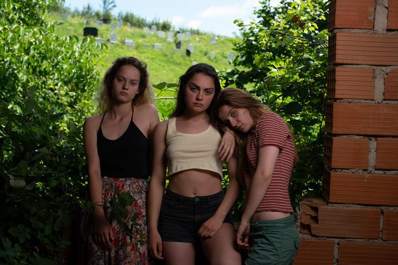 Three young women stare into the camera, their gazes unwavering in an act of defiance.   They are all dressed in summery clothes, and in the background the sun beams onto the green grass of the Kosovar hills.